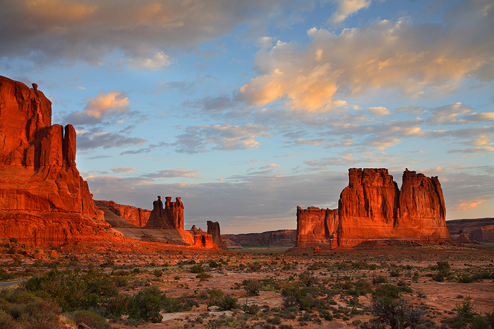 """The first rays of light bring Arches amazing sandstone formations life. In this photograph you can see the """"Three Gossips..."""