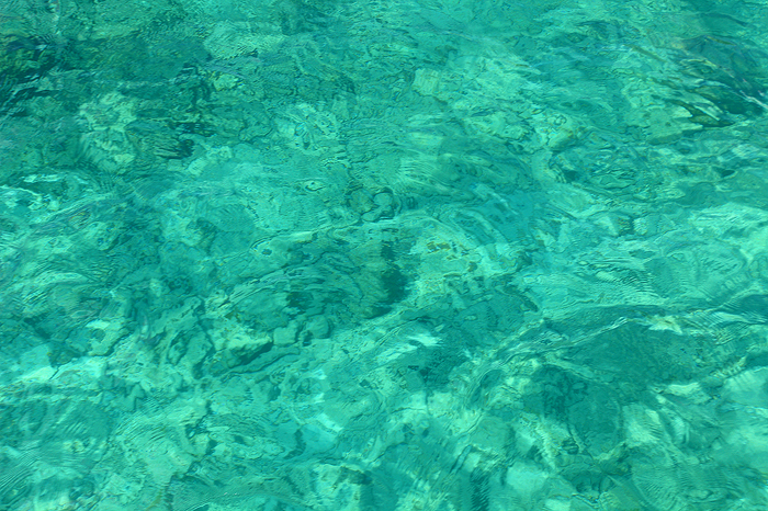 The crystal clear waters of White Bay on the Island of Jost Van Dyke as seen from the deck of a sailboat. The perfect Caribbean...