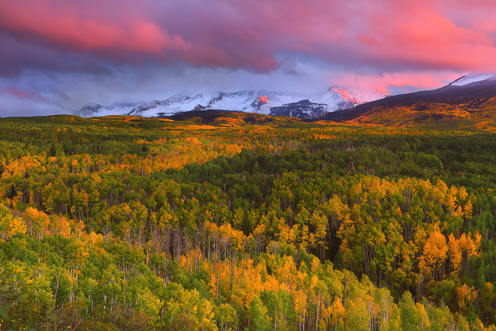 The freshly snowcapped peaks of East Beckwith Mountain briefly reveal themselves amidst a stunning autumn sunset.