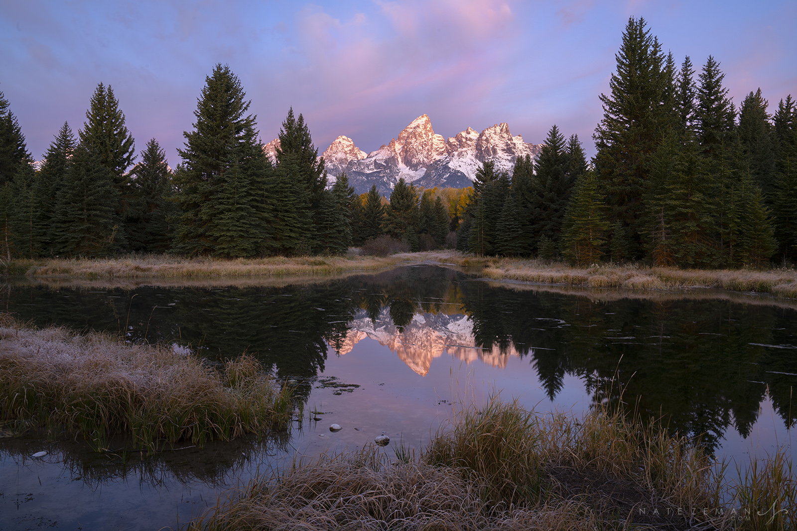 Newly dusted in autumn snow, the Tetons are perfectly reflected in a beaver pond along the Snake River.